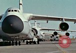 Image of  F-5E Tiger II fighters being loaded on C-5 transport aircraft California United States USA, 1976, second 7 stock footage video 65675021081