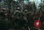 Image of U.S. soldiers dismantle and burn NVA huts in village Vietnam, 1968, second 12 stock footage video 65675021203