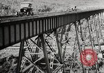 Image of Ford Model T cars driving in water, snow, & along railroad tracks United States USA, 1922, second 10 stock footage video 65675025341
