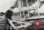 Image of Wilbur Wright adjusting transporter wheel on flyer United States USA, 1908, second 11 stock footage video 65675027433