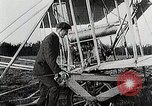 Image of Wilbur Wright adjusting transporter wheel on flyer United States USA, 1908, second 12 stock footage video 65675027433