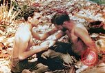 Image of Marine renders first aid to wounded buddy Saipan Northern Mariana Islands, 1944, second 1 stock footage video 65675028048