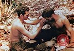 Image of Marine renders first aid to wounded buddy Saipan Northern Mariana Islands, 1944, second 4 stock footage video 65675028048