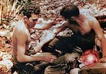 Image of Marine renders first aid to wounded buddy Saipan Northern Mariana Islands, 1944, second 6 stock footage video 65675028048