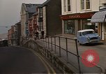 Image of U.S. sailors on Liberty explore shops  along Fortuneswell Portland England, 1967, second 11 stock footage video 65675046807