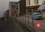 Image of U.S. sailors on Liberty explore shops  along Fortuneswell Portland England, 1967, second 12 stock footage video 65675046807