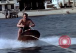 Image of motorboat pulling man and woman balanced on aquaplane United States USA, 1939, second 12 stock footage video 65675051556