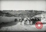 Image of Small boy walking with camels Amman Transjordan, 1945, second 8 stock footage video 65675062976
