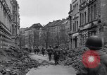 US Army soldiers advancing along ruined streets of Cologne, under fire, and breaking down a door in Cologne, Germany.
